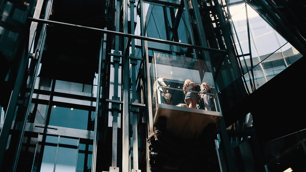 People standing in a glass elevator seen from below