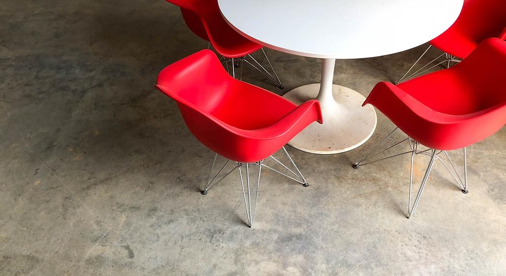 Rode stoelen en een witte tafel