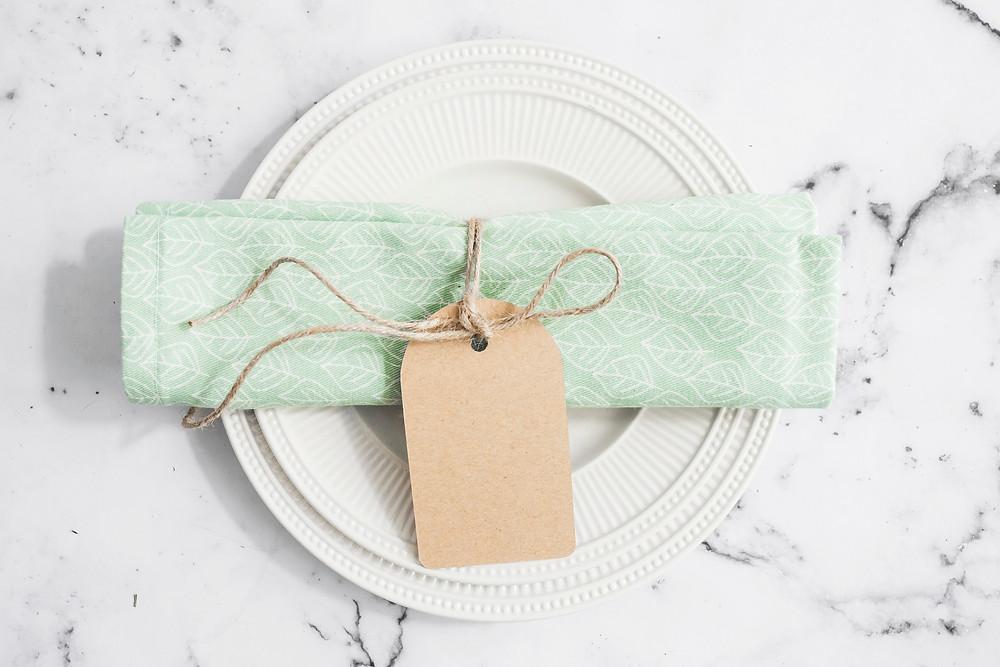 מפית עם פתק תודה לאורחים העשוי מנייר קראפט חום שקשור אליה באמצעות חוט יוטה בצבע חום