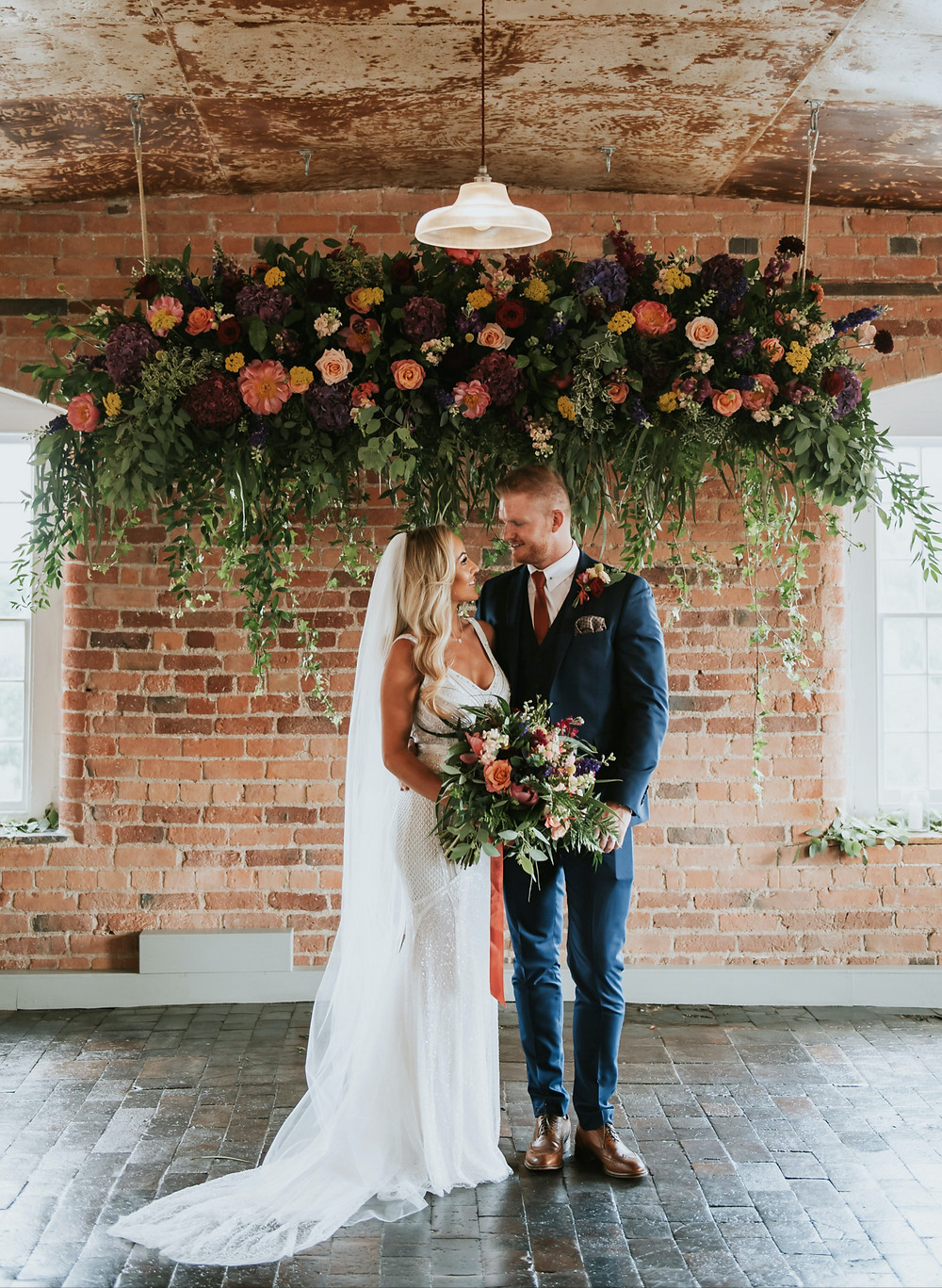 the west mill wedding ceremony with hanging flowers
