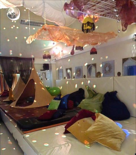 Snoezelruimte met gekleurde kussens, een tent en sfeerverlichting
