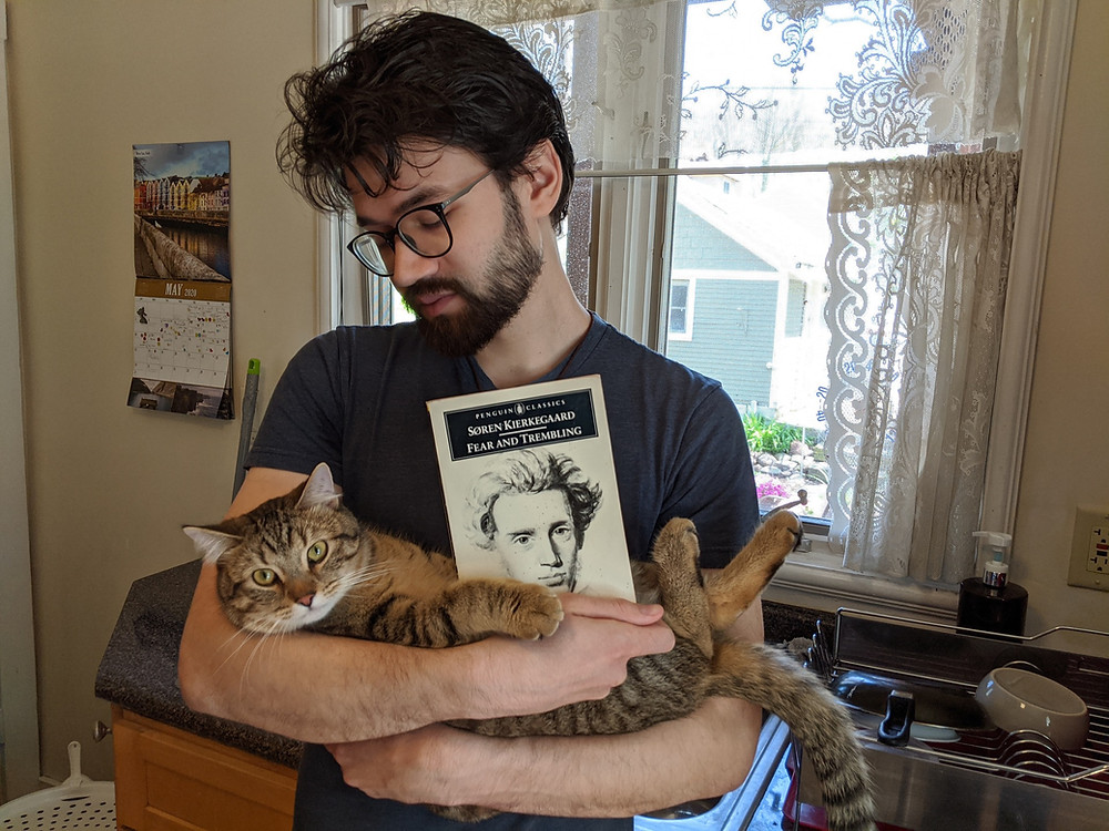 "Ilango Villoth, with his cat Whiskey, holding his copy of ""Fear and Trembling"""