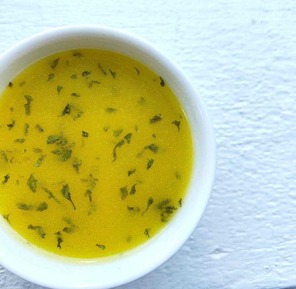 overhead shot of lemon-herb vinaigrette dressing with fresh herbs in ramekin