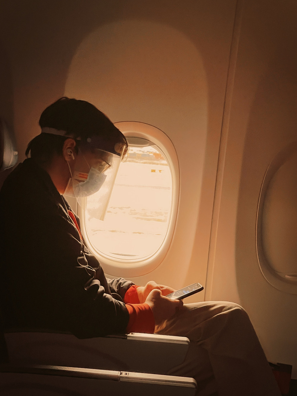 Man with mask on phone in a airplane