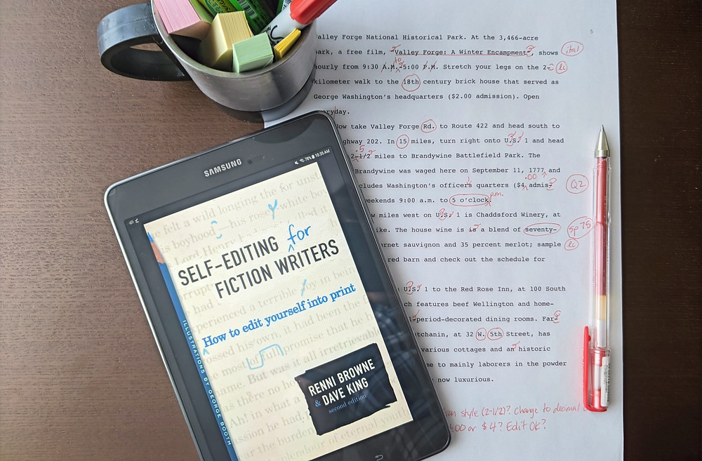 The ebook version of Self-Editing for Fiction Writers rests on a desk with an edited manuscript, a red pen, and a cup full of pens and sticky notes.