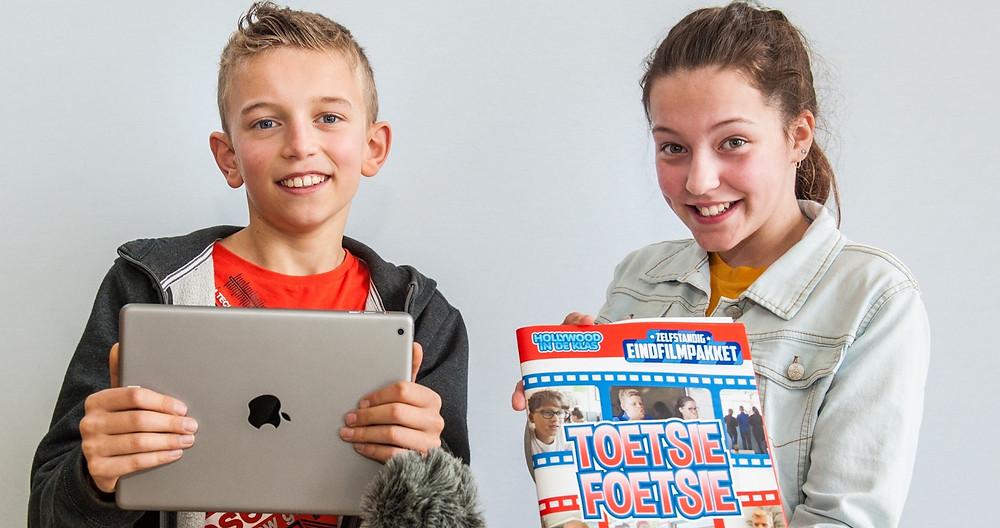 Een foto van een jongen en een meisje. De jongen (links) houdt een tablet in zijn handen. Het meisje (rechts) houdt het script van het eindfilmpakket in haar handen.