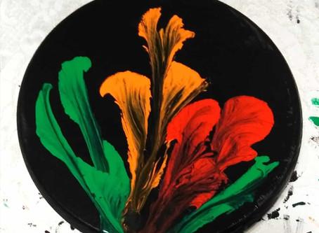 Red and orange flower on round wood