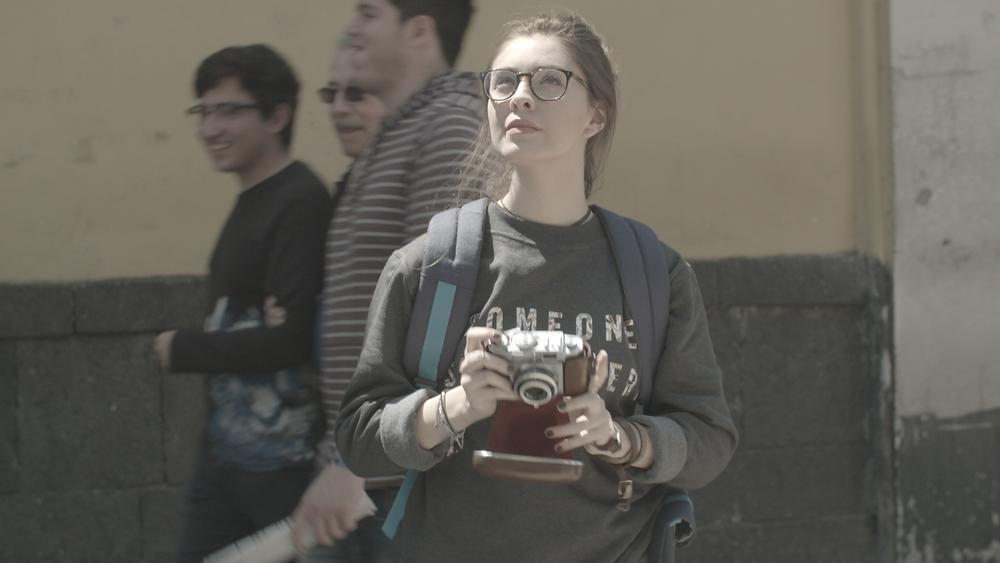 Imágen de una chica sosteniendo una cámara. La imagen tiene colores neutros y deslavados