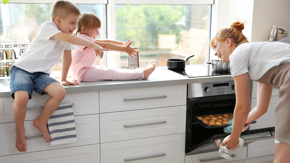 Mum in kitchen getting food out of the oven