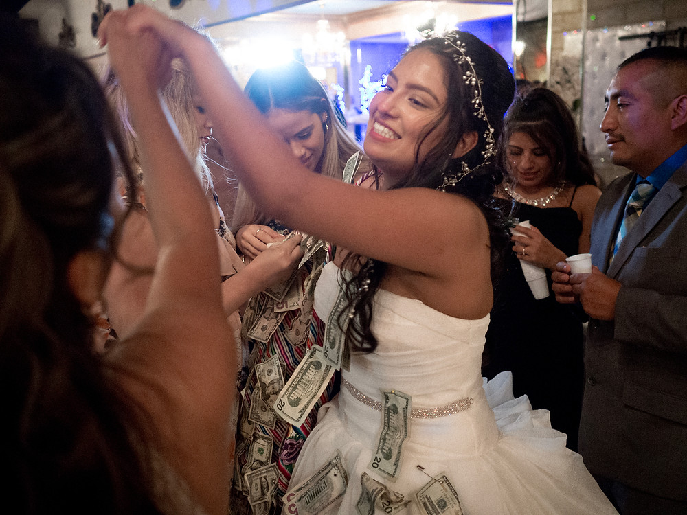 Bride smiling at friends during a dollar dance