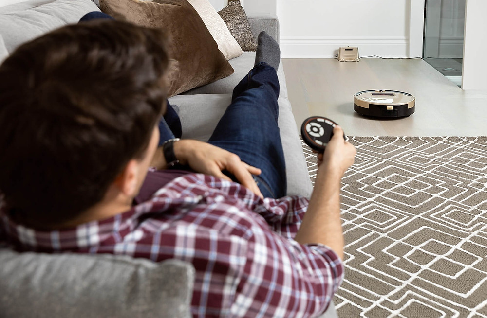 Male holding remote control with robot vacuum in front heading to charging station