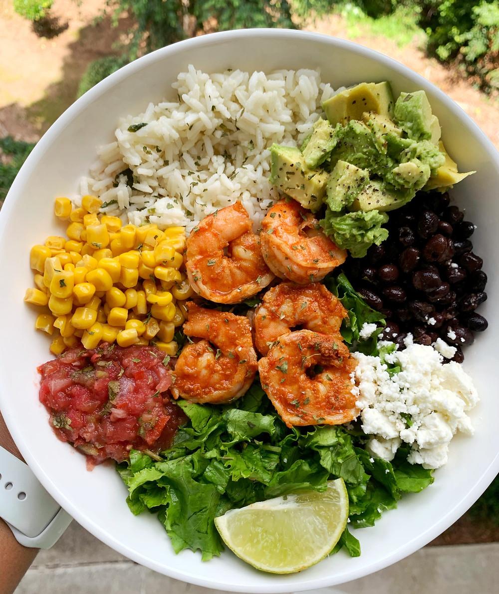 shrimp burrito bowl with cilantro-lime rice, avocado, corn, black beans, cheese, salsa, lettuce, and lime