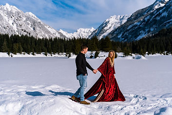 A bride wearing a red dress walking in front of a snowy, frozen lake during their adventure elopement in Washington