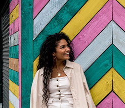 Colorful Liverpool wall behind personal trainer, Mia Eyo.