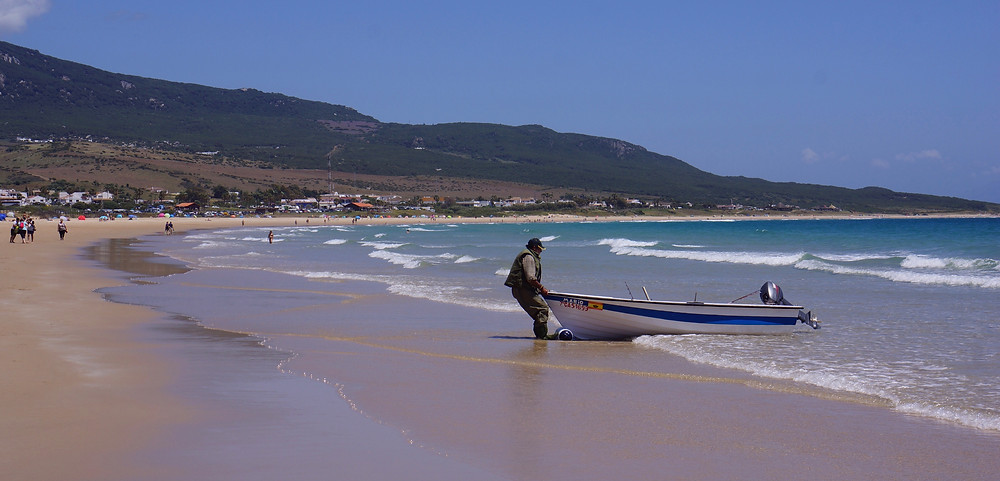 Long, quiet, sandy beach at Bolonia with fisherman and boat.