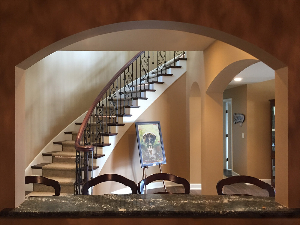 Curved stair with metal pickets is framed by an arched window in the lower level bar.