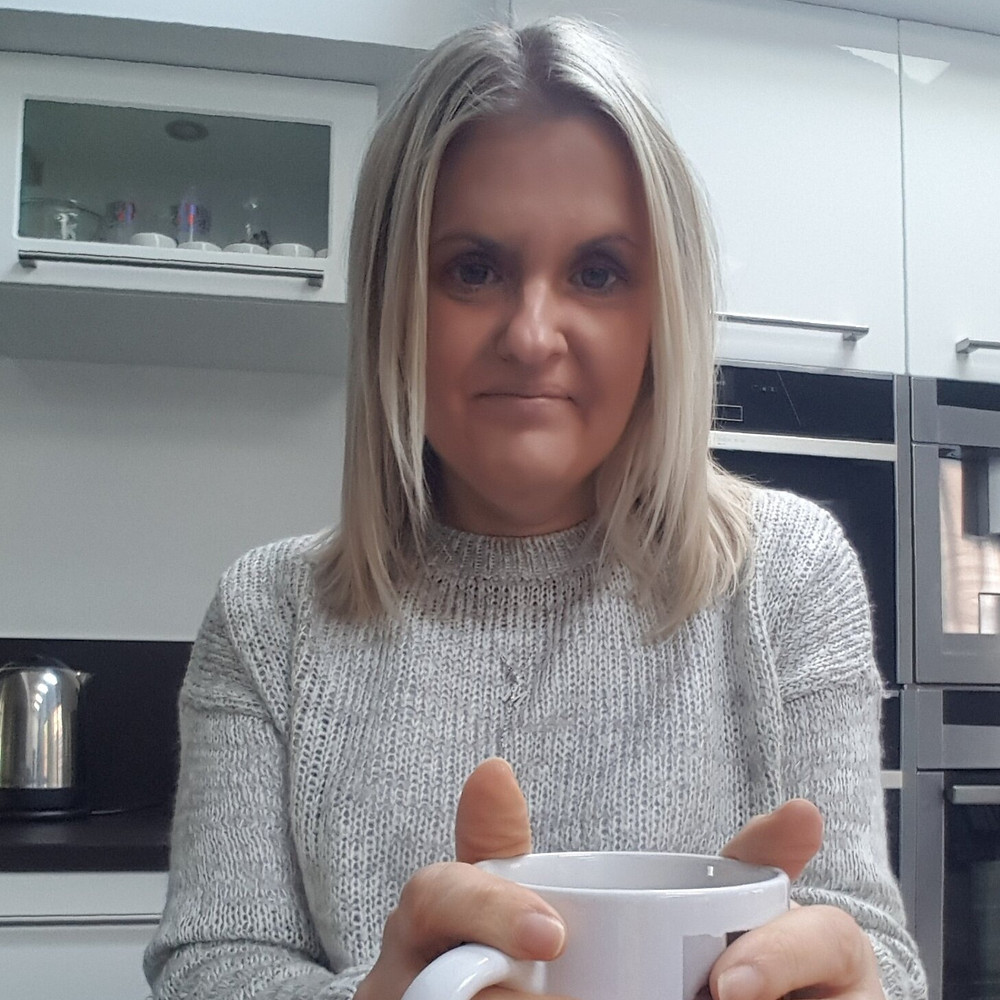 support worker Michelle Wade smiling in her kitchen while holding a mug
