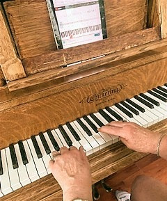 Photo of an upright piano keyboard being played with an iPad on the music stand