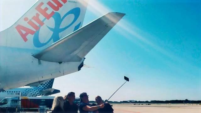 אנשים מצטלמים ליד מטוס