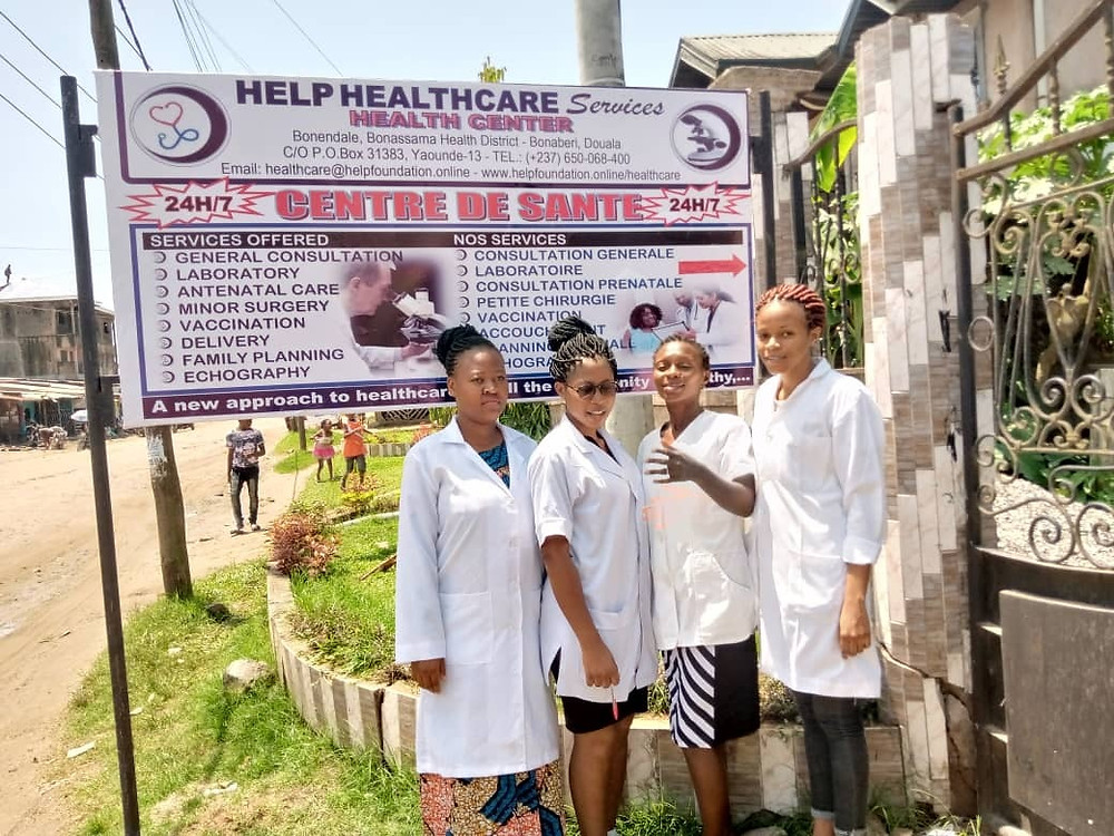 HELP HealthCare Services, Bonendale - Douala. Four members of the nursing team beside the center's signpost.