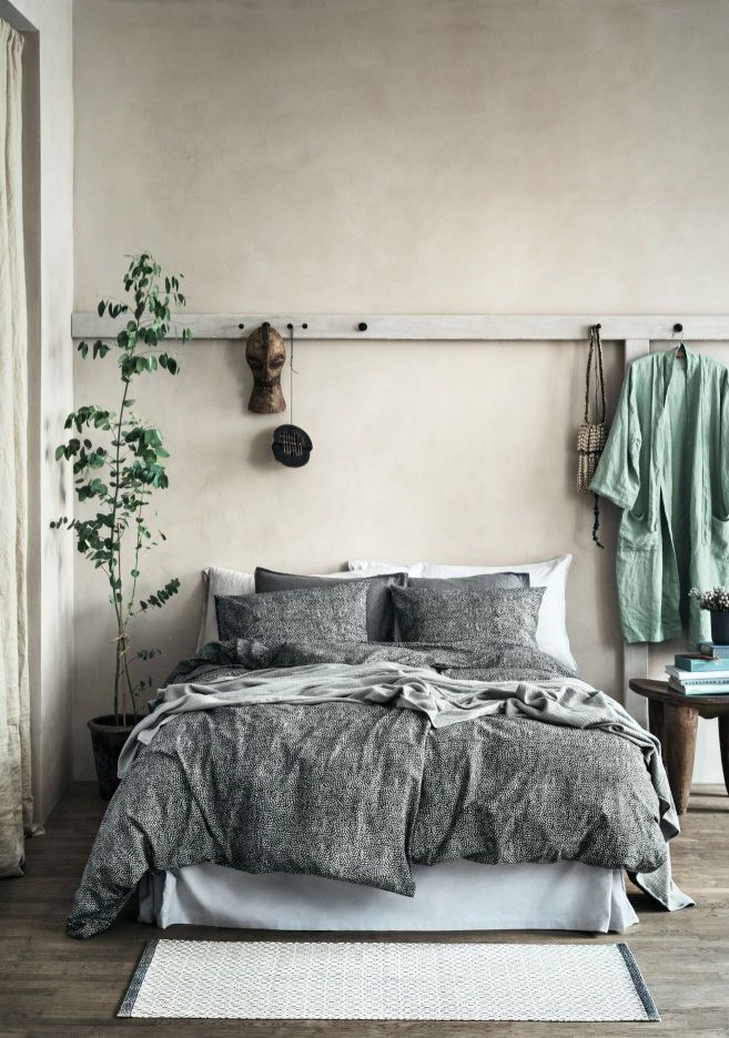 Naturally looking bedroom decor with grey linen and potted tree next to the bed.