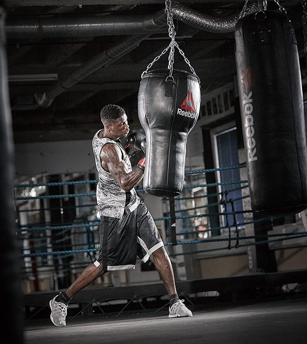 a boxer in a boxing gym hitting an uppercut punch bag