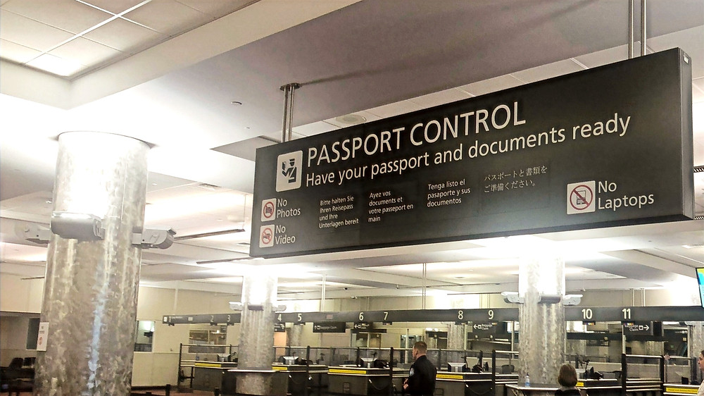 "A sign which reads ""passport control. Have your passport and documents ready"". On the bottom it states ""no photos, no video, and no laptops""."