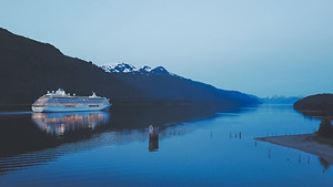 Cruise ship Crystal Serenity and reflection in the water as it approaches Juneau in Alaska