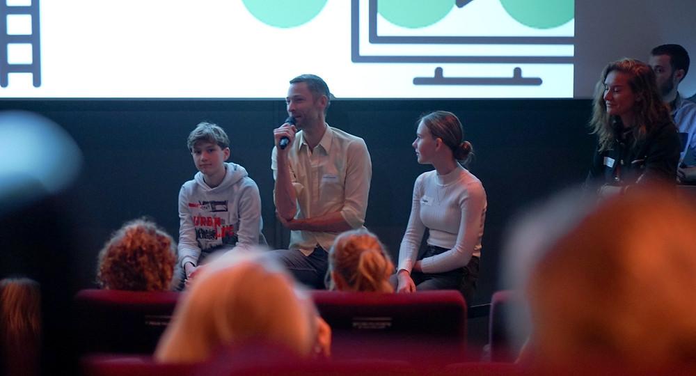 Een foto van een theater waarin een man met twee kinderen op het podium zit. De man in het midden heeft een microfoon in zijn handen en is aan het woord.