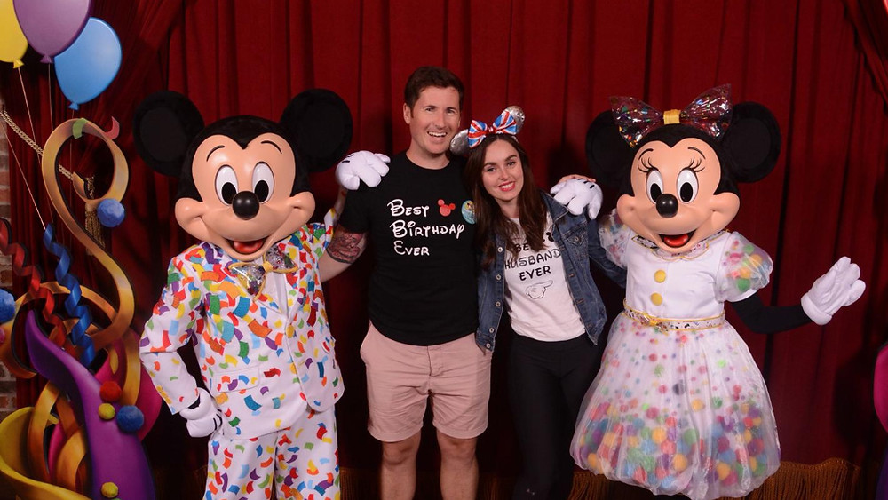 A couple celebrate their visit to Disney's Magic Kingdom with a meet and greet with Mickey Mouse and Minnie Mouse