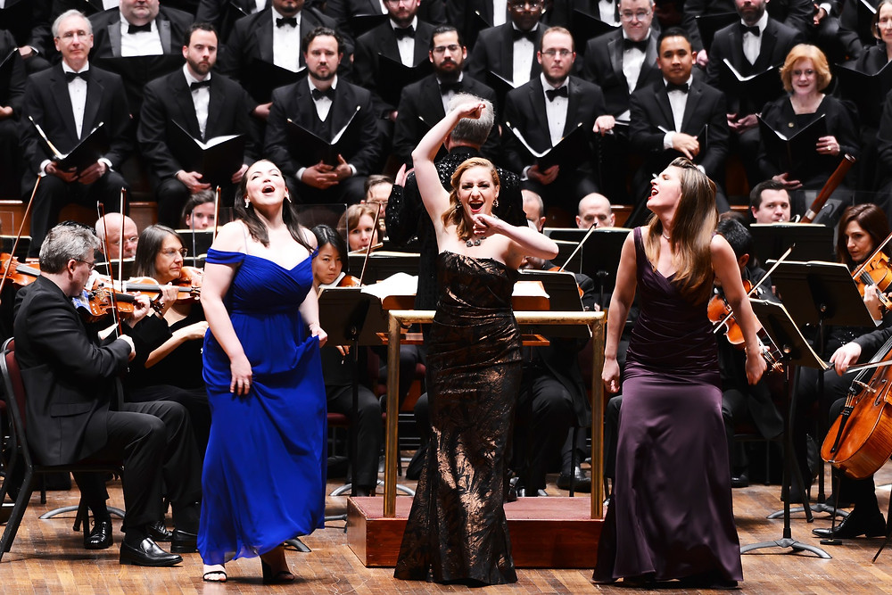 Three women singing in front of an orchestra