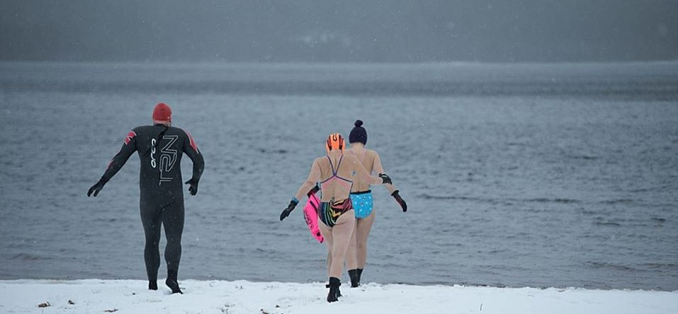 Winter Open Water Swimmers taking the plunge in a Scottish Loch with Snow on the ground