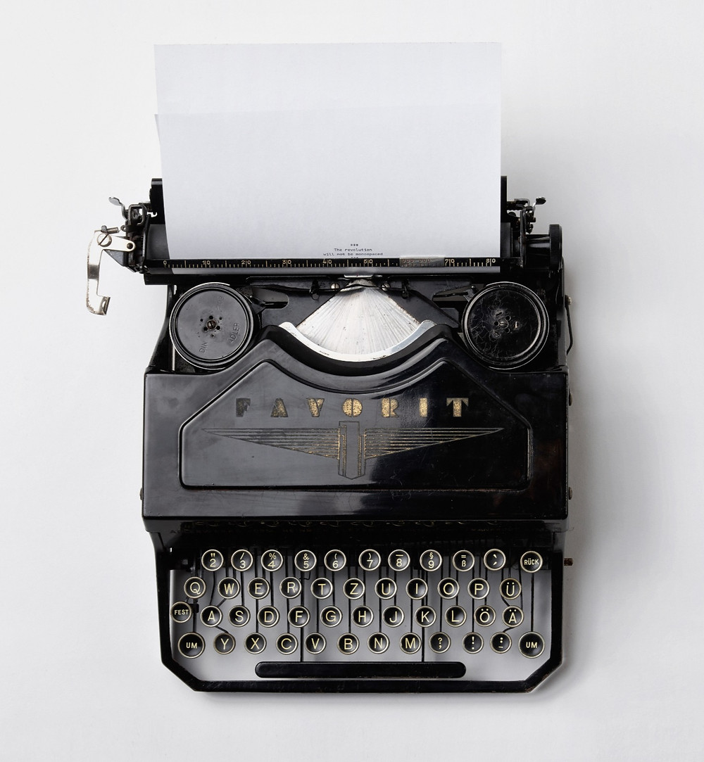 Classic typewriter with blank piece of white paper.