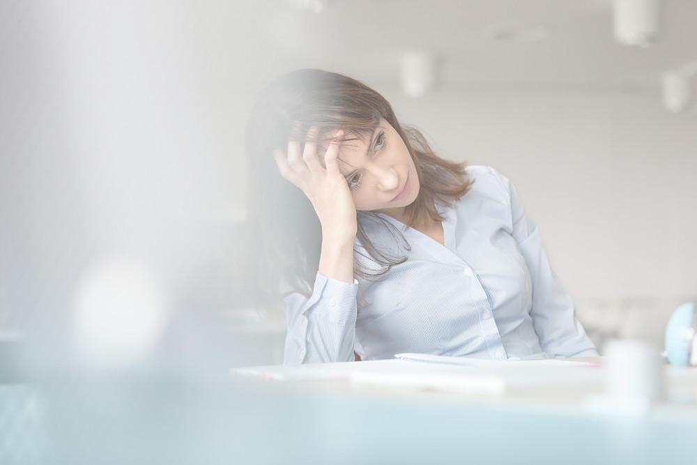 Gestresste berufstätige Frau am Arbeitsplatz