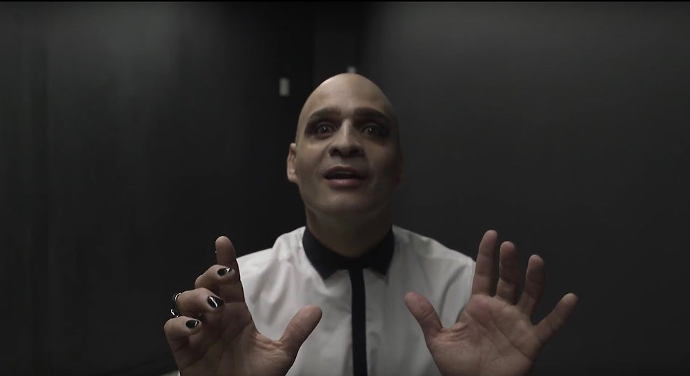 A man dressed in a white and black shirt stands with his hands out stretching in a black room. His eyes are menacing with his mouth slightly agape.