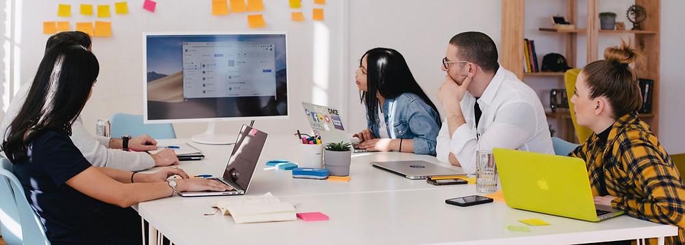 Imagem de uma sala de reunião com 5 pessoas olhando para um monitos com uma apresentação. A imagem tem o intuito de mostrar como o isolamento acústico está relacionado às salas de reunião.