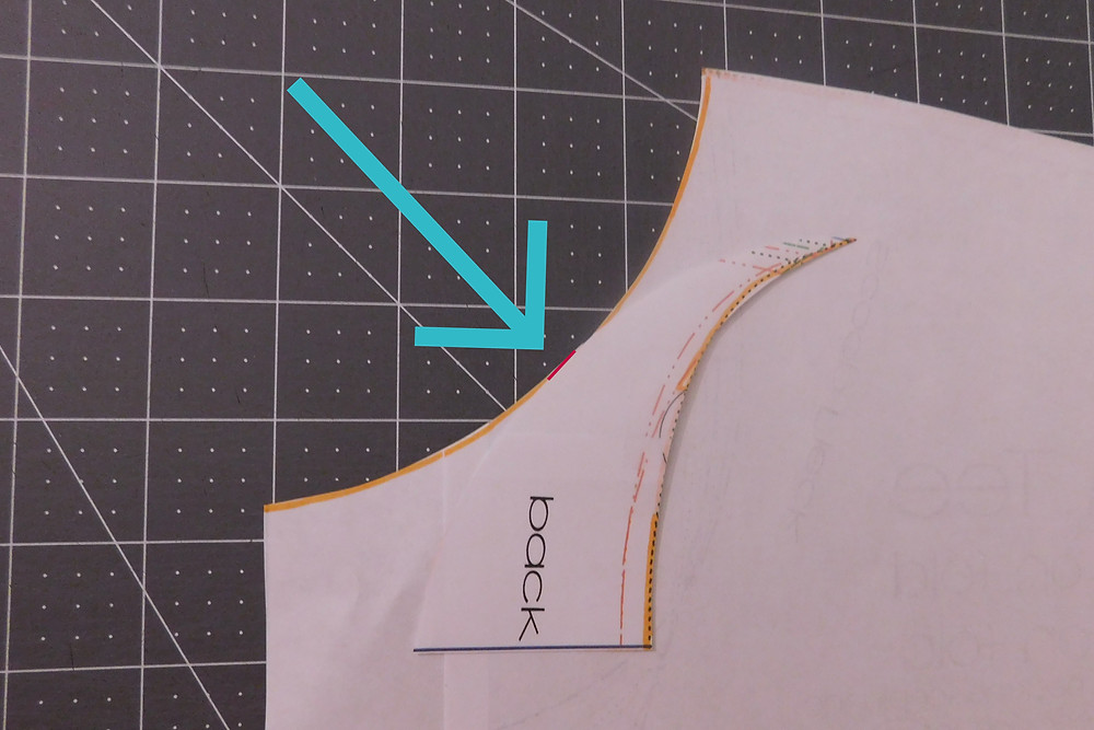 "Image of the pattern piece with the front neckline piece trimmed to leave a small 1/2"" piece near the center still attached. That small piece is highlighted with a short red line and has a blue arrow pointing to it."