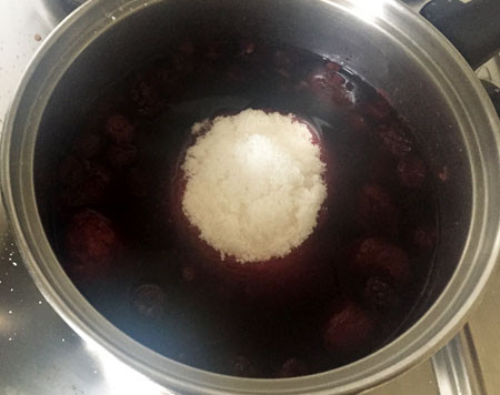 Left: Strawberries, blackberries, blueberries and raspberries with water. Right: After cooking for an hour, an equal weight of jam sugar is added (castor sugar with pectin).