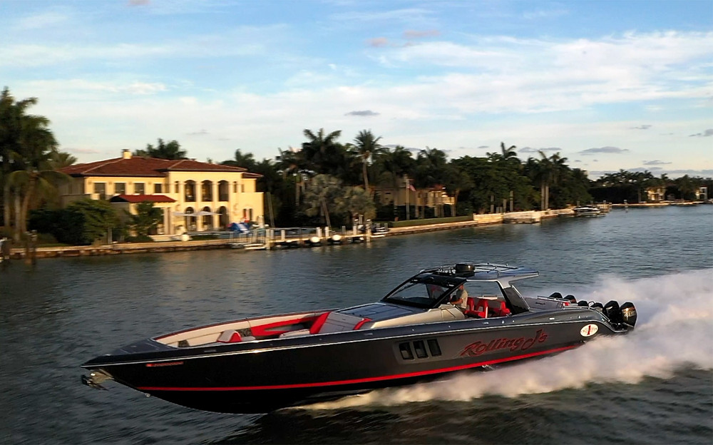 Beautiful black cigarette boat with red and grey interior  drives by mega mansion on Miami's Biscayne Bay