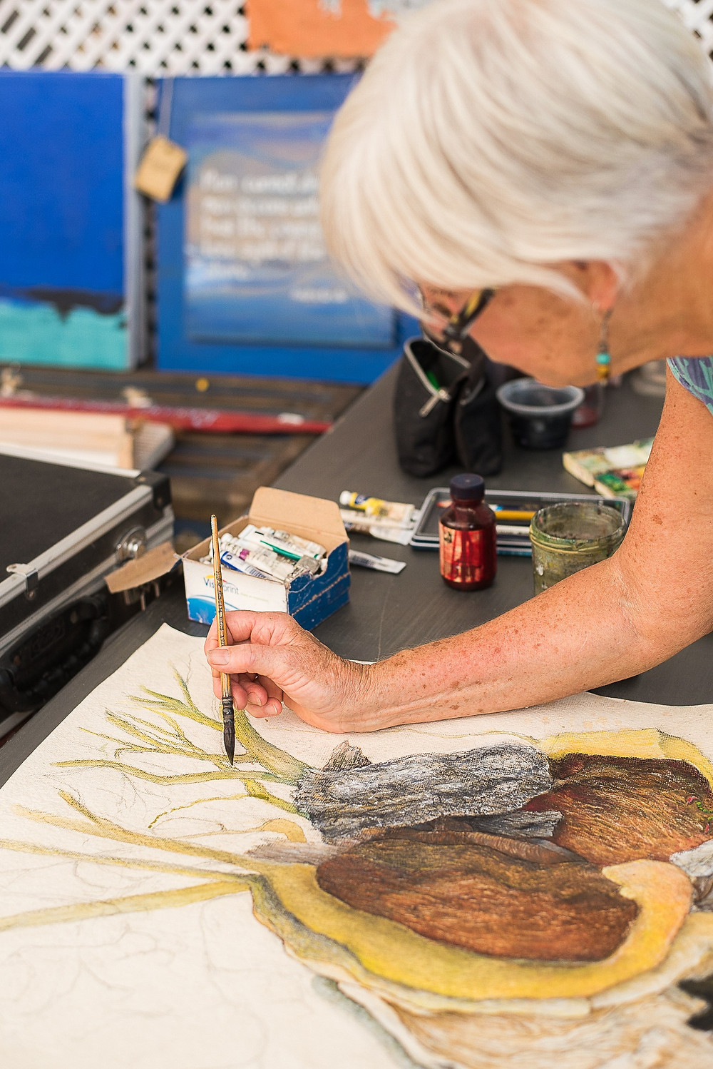 A white haired woman wearing glasses is bending over an artwork that she is working on. The artwork is a large drawing of hat appears to be a hollowed-out tree. On the table behind the artist you can see some of the materials she has been using - a pot of ink, a box of watercolours.