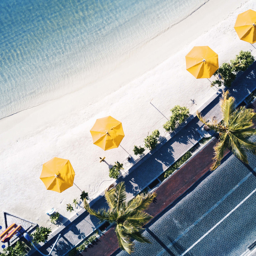 Aerial view of a tranquil beach with yellow umbrellas lined up.