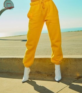 Woman wearing a yellowtrack pants and white boots