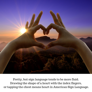 Close up of a pair of hands with the fingers in the shape of a heart against a vivid sunlit mountainous landscape.