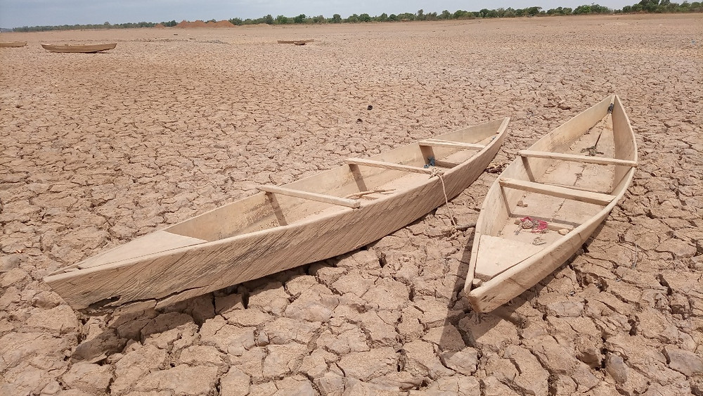 Global warming causes intense and permanent droughts. Two wood boats laying on dried soil where used to be a lush lake.