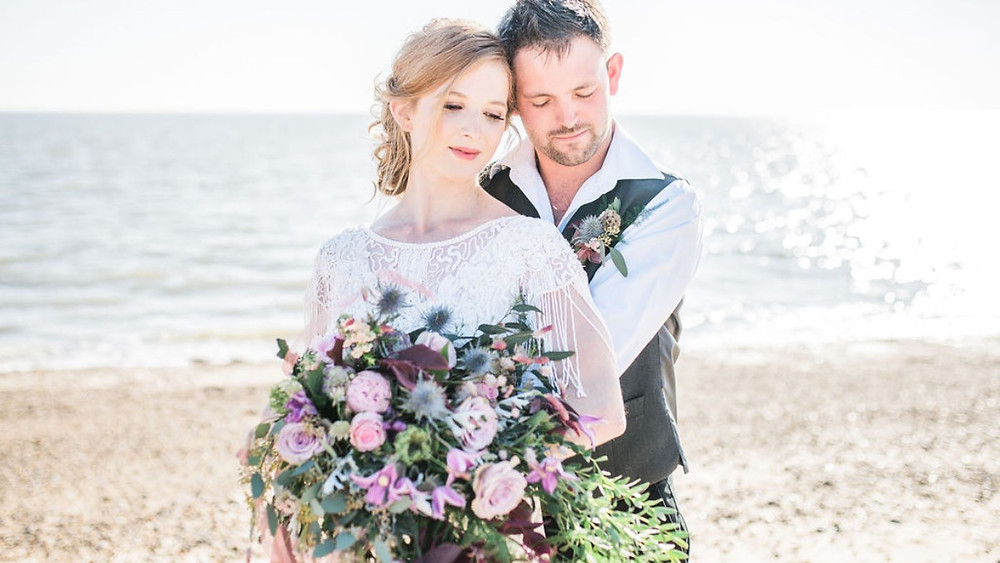 Beach elopement with bride and groom on beach lace tasselled Poppys Perspective wedding dress and bouquet with thistles