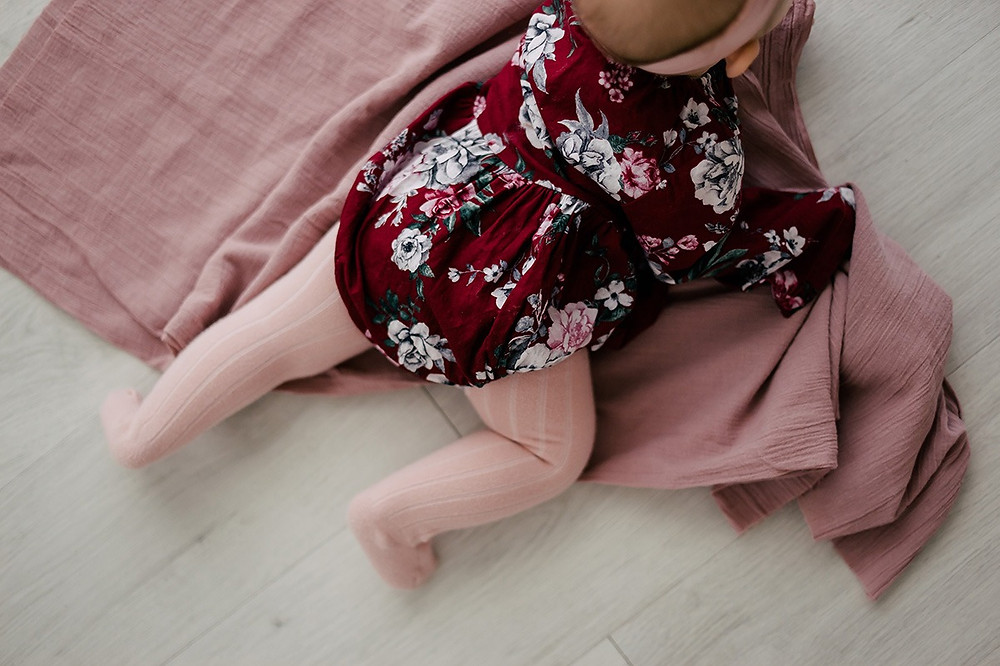 baby girl wearing floral onesie and pink ribbed tights laying on pink blanket