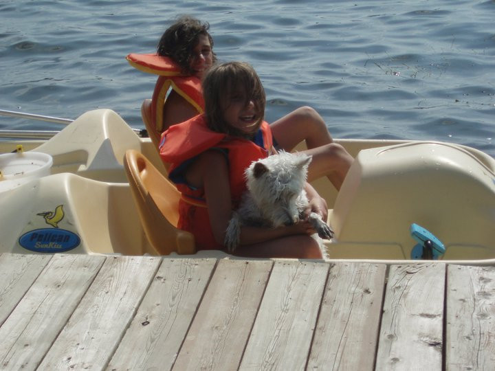 two children sitting in a pedal boat with a little Westie.