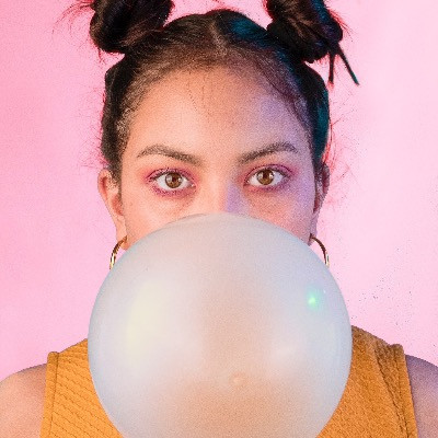 A woman blowing a bubblegum bubble with xylitol