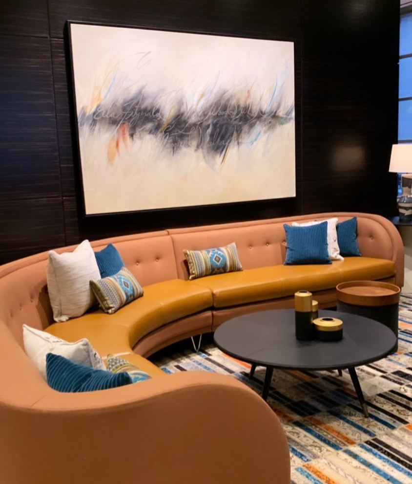 Tannish orange leather couch with blue pillows