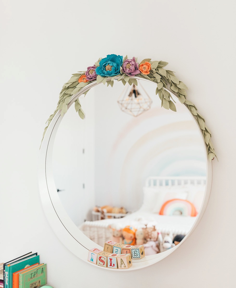 A colourful felt floral garland laying on top of a round white mirror above a child's wooden dresser in a rainbow bedroom.